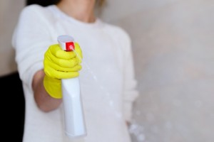hand with yellow rubber gloves holding detergent spray bottle and spraying in bathroom